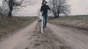 Junger Mann, der mit seinem Hund entlang dem Schotterweg geht stock video