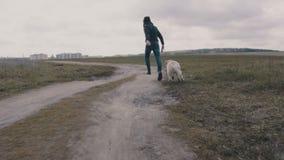 Junger Mann, der mit seinem Hund entlang dem Schotterweg läuft stock video