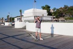 junger Mann, der mit Skateboard und Handy aufwirft Stockfotos