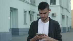 Junger Mann, der mit Smartphone geht stock video