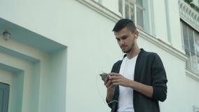 Junger Mann, der mit Smartphone geht stock footage
