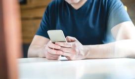 Junger Mann, der mit Smartphone simst Kerl, der Handy verwendet stockbild