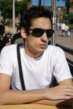 Junger Mann, der mit Sonnegläsern sitzt Lizenzfreies Stockfoto