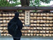 Junger Mann, der mit traditionellem hölzernem Gebetsbrett ema betet lizenzfreie stockfotos