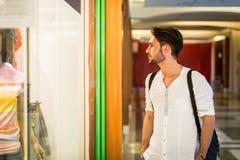 Junger Mann, der Mode-Einzelteile im Shop-Fenster betrachtet stockfoto