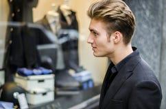 Junger Mann, der Mode-Einzelteile im Shop-Fenster betrachtet lizenzfreie stockfotos