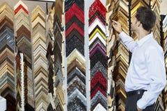 Junger Mann, der multi farbige Rahmen im Speicher betrachtet Stockfoto