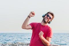Junger Mann, der Musik auf Kopfhörern hört Stockbilder