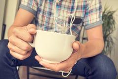 Junger Mann, der Musik beim Trinken eines Kaffees oder des Tees hört Lizenzfreie Stockfotografie