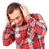 Junger Mann, der Musik lokalisiert auf weißem Hintergrund hört stockfotografie