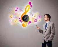Junger Mann, der Musik mit musikalischen Anmerkungen singt und hört Stockbild
