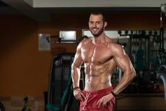 Junger Mann, der Muskeln biegt Stockfoto