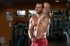 Junger Mann, der Muskeln biegt Stockfotos