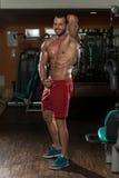 Junger Mann, der Muskeln biegt Stockfotografie