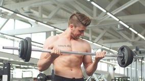 Junger Mann, der Muskeln mit Barbell in der Turnhalle biegt stock footage