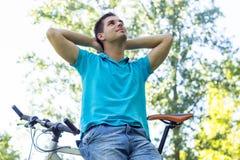 Junger Mann, der nach einer Fahrradfahrt stillsteht lizenzfreies stockbild