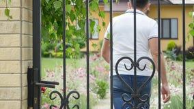 Junger Mann, der nach Hause, öffnend, schließend Tor, Yard, Sommer kommt stock video footage