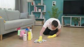 Junger Mann, der nachdem dem Bewegen auf neue Wohnung aufr?umt Neues Hauptreinigungskonzept stock video footage