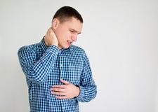 Junger Mann, der Nackenschmerzen hat auf Grau Stockbild
