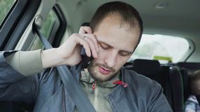 Junger Mann der Nahaufnahme, der am Handy beim Reiten in Rücksitz des Autos spricht stock video