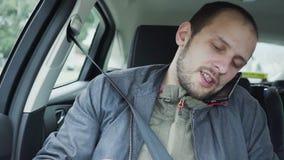 Junger Mann der Nahaufnahme, der am Handy beim Reiten in Rücksitz des Autos spricht stock footage