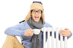Junger Mann, der nahe bei dem Heizkörper hält Schale heißen Tee sitzt Lizenzfreie Stockbilder