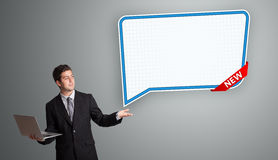 Junger Mann, der nahe bei modernem Spracheblasenkopienraum und h steht Stockfoto