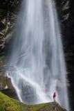 Junger Mann, der nahe einem großen Wasserfall steht Stockfotografie