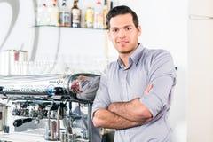 Junger Mann, der nahe einer modernen automatischen Kaffeemaschine aufwirft Stockfoto