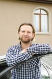 Junger Mann, der nahe seinem Auto und Haus und Lächeln steht Stockfoto