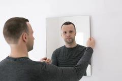 Junger Mann, der nahe weißer Wand mit Spiegel steht Lizenzfreie Stockfotografie