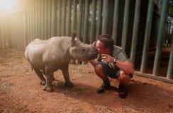 Junger Mann, der Nashornbaby küsst lizenzfreie stockfotos