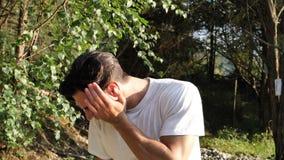 Junger Mann in der Natur, die unter Zahnschmerzen leidet stock footage