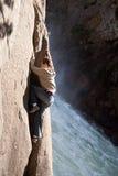 Junger Mann, der neben Wasserfall steigt Lizenzfreie Stockfotografie