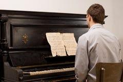 Junger Mann, der Noten auf einem Klavier spielt lizenzfreie stockbilder