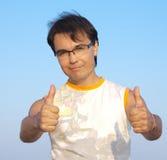 Junger Mann, der o.k. am Hintergrund des blauen Himmels darstellt Stockfotografie