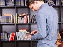 Junger Mann, der oben Informationen in einem Buch schaut Stockfotos