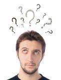 Junger Mann, der oben mit Fragezeichen schaut Lizenzfreie Stockbilder