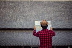 Junger Mann, der in der offenen Karte schaut Reisendstellung mit Straßenkarte I lizenzfreie stockbilder