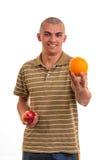 Junger Mann, der Orange anstelle des roten Apfels anbietet Lizenzfreies Stockfoto
