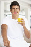 Junger Mann, der Orangensaft trinkt Stockbild
