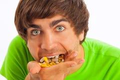 Junger Mann, der Pillen sich speist Lizenzfreie Stockfotos