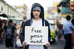 Junger Mann, der Plakat für Aspiration im Freien hält stockbild
