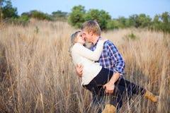 Junger Mann, der playfully seine Freundin für einen Kuss aufhebt Lizenzfreies Stockfoto