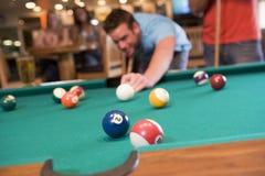 Junger Mann, der Pool in einem Stab spielt Lizenzfreie Stockfotos