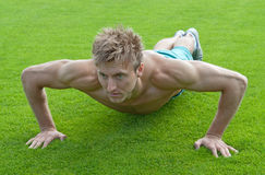 Junger Mann, der Push-ups auf grünem Gras tut Stockbilder