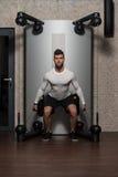 Junger Mann, der Rückenübungen in der Turnhalle tut Stockbild