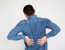 Junger Mann, der Rückenschmerzen hat Auf Weiß stockfotos