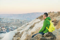 Junger Mann, der am Rand der Klippe, Cappadocia, die Mittel-Türkei sitzt Lizenzfreie Stockfotos