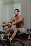 Junger Mann, der Rückenübungen in der Turnhalle tut Stockbilder